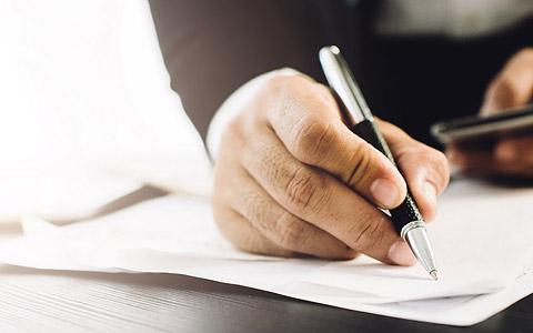Abbildung: Schreibende Person mit Stift und Zettel