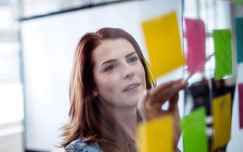 Abbildung: Rothaarige Frau + PostIts und Kollegen hinter Glasfront